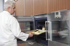 Mannelijke Chef-kok Placing Baking Tray In Oven royalty-vrije stock foto