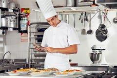 Mannelijke Chef-kok Using Digital Tablet in Keuken Stock Afbeelding