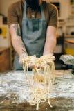 Mannelijke chef-kokhanden met ongekookte eigengemaakte deegwaren stock foto