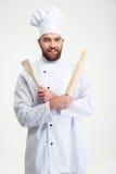 Mannelijke chef-kokkok die een deegrol en een lepel houden Royalty-vrije Stock Foto's