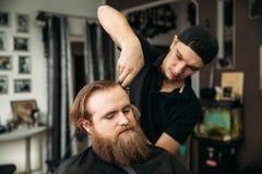 Mannelijke cliënt die kapsel door kapper krijgen stock fotografie