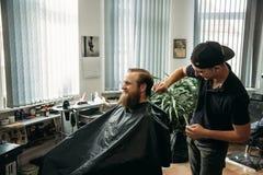 Mannelijke cliënt die kapsel door kapper krijgen royalty-vrije stock foto's