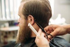 Mannelijke cliënt die kapsel door kapper krijgen stock foto