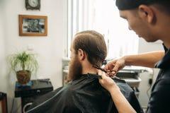Mannelijke cliënt die kapsel door kapper krijgen Achter mening royalty-vrije stock afbeeldingen