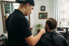 Mannelijke cliënt die kapsel door kapper krijgen Achter mening stock afbeelding