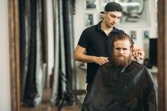 Mannelijke cliënt die kapsel door kapper krijgen barbershop stock afbeeldingen
