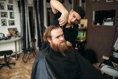 Mannelijke cliënt die kapsel door kapper krijgen barbershop stock fotografie
