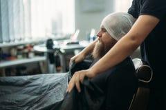 Mannelijke cliënt met nat hoofd die kapsel door kapper in kapperswinkel krijgen stock foto