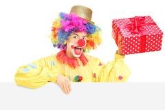 Mannelijke clown met vrolijke uitdrukkingsholding huidig achter spatie Stock Fotografie