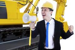 Mannelijke contractant met megafoon en graafwerktuig Royalty-vrije Stock Foto