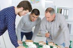 Mannelijke contractanten die bouwplan ontwikkelen - bedrijfsschoolconcept stock foto's