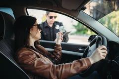 Mannelijke cop in eenvormig schrijft een boete aan vrouwelijke bestuurder royalty-vrije stock fotografie