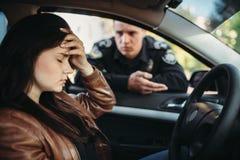 Mannelijke cop in eenvormige controle vrouwelijke bestuurder op weg royalty-vrije stock fotografie