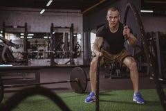 Mannelijke crossfitatleet die met slagkabels bij gymnastiek uitwerken stock afbeelding