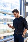 Mannelijke deskundige manager die programma's over cellphone gebruiken, die zich in groot bedrijf bevinden royalty-vrije stock afbeelding