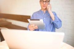 Mannelijke deskundige werknemer die op celtelefoon spreken en aanrakingsstootkussen met netto-boek gebruiken stock foto's