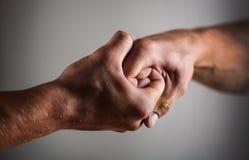 Mannelijke die hand in handdruk wordt verenigd De handen van de mensenhulp, voogdij, bescherming Twee handen, wapen, die hand van stock afbeeldingen