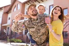 Mannelijke die militair met zijn familie wordt herenigd, in openlucht Legerdienst royalty-vrije stock foto's