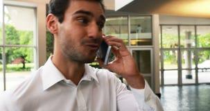 Mannelijke directeur die op mobiele telefoon spreken stock videobeelden