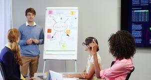 Mannelijke directeur die stroomschema op whiteboard bespreken met medewerkers stock video