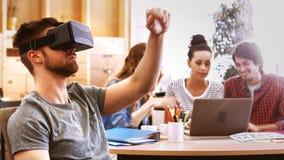 Mannelijke directeur die virtuele werkelijkheidshoofdtelefoon met behulp van terwijl collega's die bij bureau op elkaar inwerken stock videobeelden