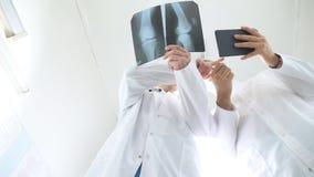 Mannelijke dokters die tabletpc met behulp van terwijl elkaar over x ray beeld van patiënt raadpleeg Medische arbeiders in het zi stock video
