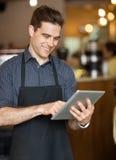 Mannelijke Eigenaar die Digitale Tablet in Cafetaria gebruiken royalty-vrije stock afbeelding