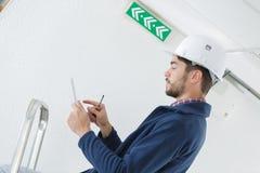 Mannelijke elektricien die zich op trapladder bevinden die licht herstellen royalty-vrije stock afbeeldingen