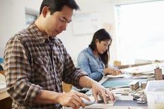 Mannelijke en Vrouwelijke Architect Working On Model in Bureau stock afbeeldingen