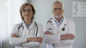 Mannelijke en vrouwelijke arts die camera bekijken die wapens, reclame, waarborg kruisen stock video