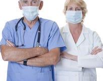 Mannelijke en vrouwelijke arts die maskers dragen Stock Fotografie