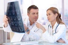 Mannelijke en vrouwelijke artsen die in bureau raadplegen Royalty-vrije Stock Foto's