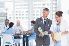 Mannelijke en vrouwelijke artsen met rapporten Royalty-vrije Stock Foto's