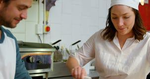 Mannelijke en vrouwelijke bakker die deegwarensnijder in keuken 4k met behulp van stock footage