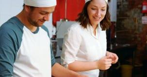 Mannelijke en vrouwelijke bakker die raviolizegel op deegwarendeeg 4k gebruiken stock videobeelden