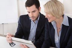 Mannelijke en vrouwelijke bedrijfsmensen die het scherm van een tablet bekijken stock fotografie
