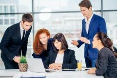 Mannelijke en vrouwelijke bedrijfsmensen rond laptop computer in bureau royalty-vrije stock afbeeldingen
