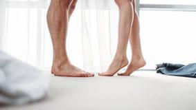 Mannelijke en vrouwelijke benen, vertrouwelijke spelen in slaapkamer stock fotografie