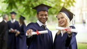 Mannelijke en vrouwelijke diploma's tonen en gediplomeerden die, volledig hoger onderwijs glimlachen royalty-vrije stock afbeeldingen