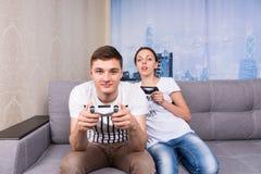 Mannelijke en vrouwelijke gamers die videospelletje spelen stock afbeeldingen