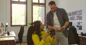 Mannelijke en vrouwelijke grafische ontwerpers die over digitale tablet bij bureau 4k bespreken stock footage