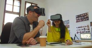 Mannelijke en vrouwelijke grafische ontwerpers die virtuele werkelijkheidshoofdtelefoon met behulp van bij bureau 4k stock videobeelden
