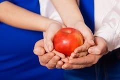 Mannelijke en vrouwelijke handen die appel houden Royalty-vrije Stock Afbeelding