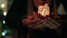 Mannelijke en vrouwelijke handen die lichtgevend huis houden stock footage