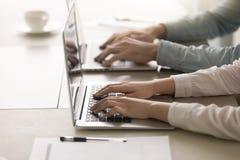 Mannelijke en vrouwelijke handen op toetsenbord, die aan laptop, close-up werken stock foto's