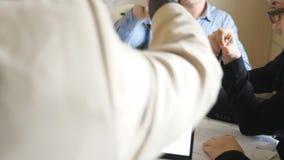 Mannelijke en vrouwelijke handen van medewerkers die grafieken in bureau onderzoeken Wapens van bedrijfsmensen die financiële ver stock footage