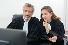 Mannelijke en vrouwelijke magistraten die computer bekijken royalty-vrije stock foto's