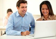 Mannelijke en vrouwelijke medewerker die laptop bekijken stock foto