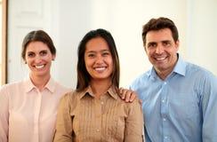 Mannelijke en vrouwelijke medewerkers die bij u glimlachen stock foto