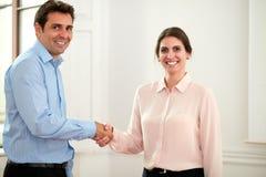 Mannelijke en vrouwelijke medewerkers die handen het begroeten geven stock foto